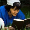 boy lying next to soccer ball reading book with a smile