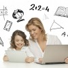 mother helping daughter with homework using tablet and laptop