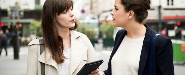 two casual businesswomen talking listening